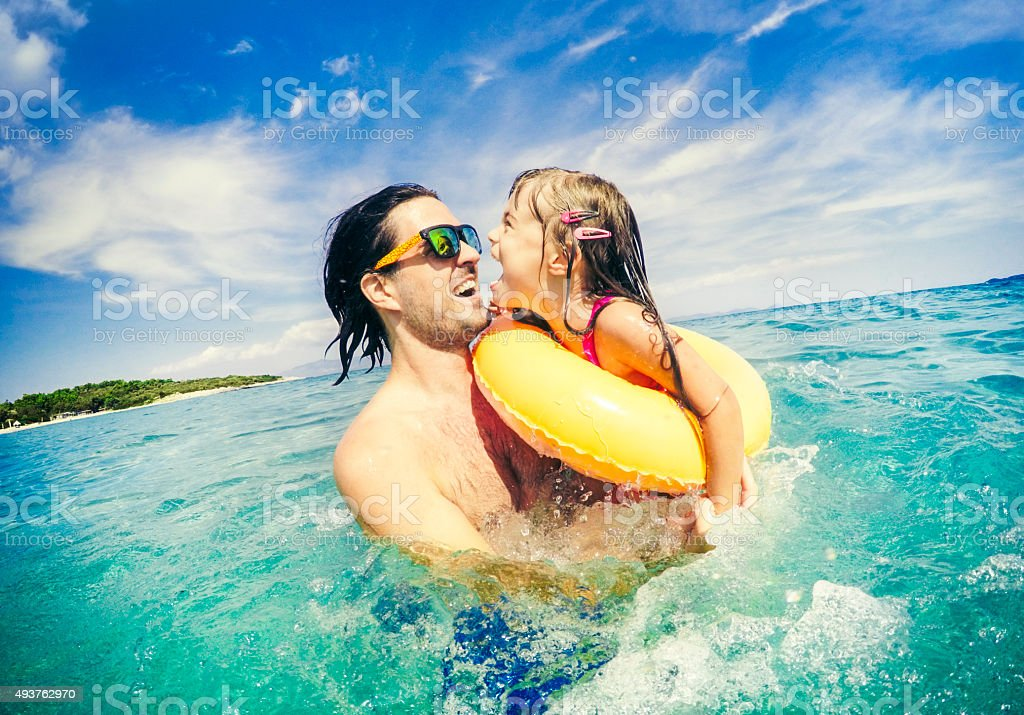 Father and child jumping together in sea stock photo