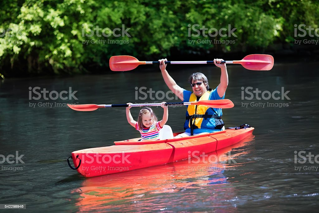 Father and child kayaking in summer stock photo