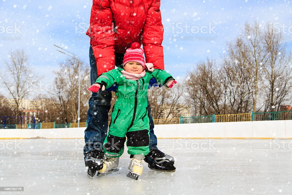 father and child learning to skate in winter stock photo