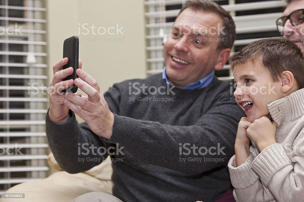 Father and child looking at mobile phone stock photo