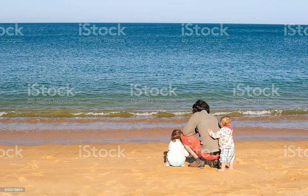 Father and children at sea stock photo