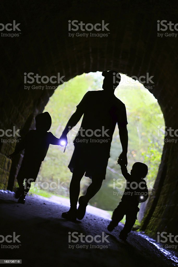 Father and Children Exploring Dark Tunnel stock photo
