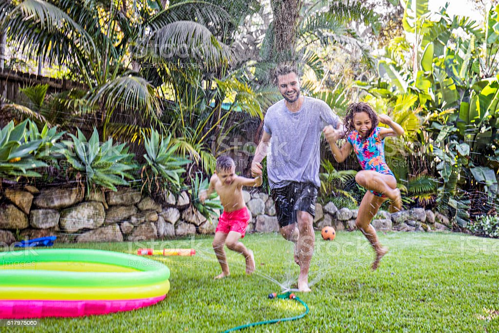Father and children jumping in sprinkler stock photo
