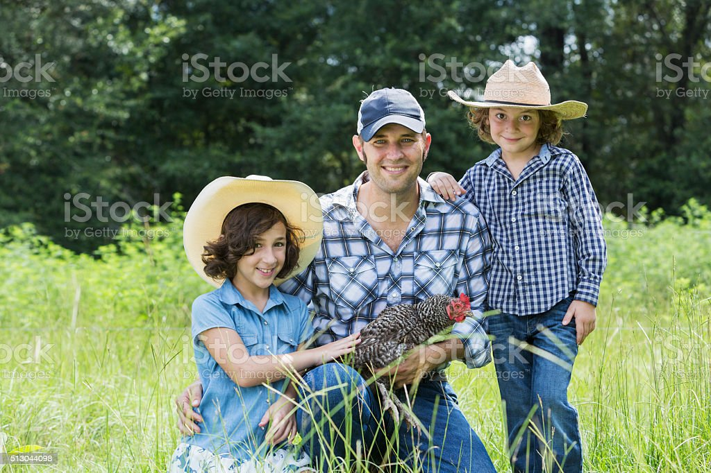 Father and children on family farm holding a chicken stock photo