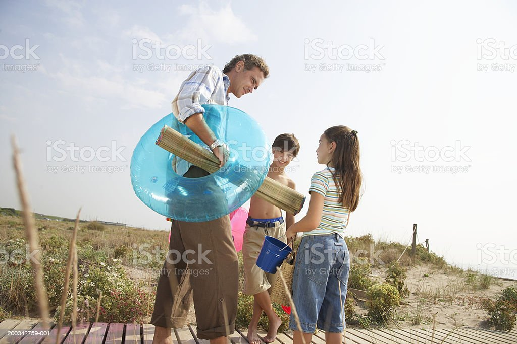 Father and children (7-9) on path carrying beach mat and toys stock photo