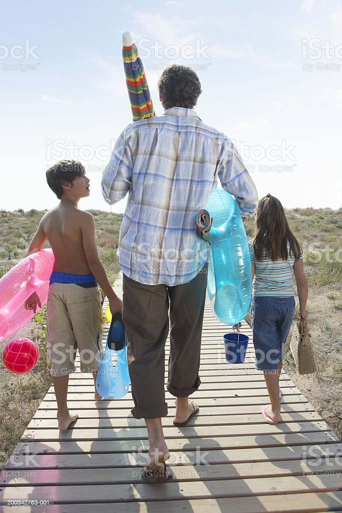Father and children (7-9) on path carrying beach toys, rear view royalty-free stock photo