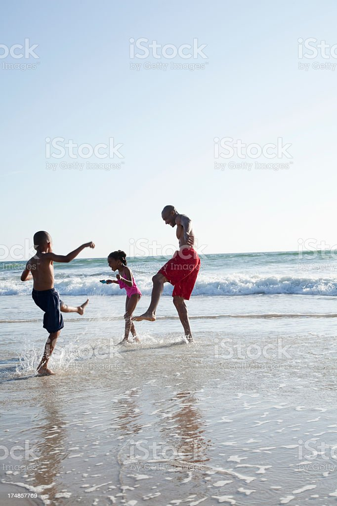 Father and children playing in water at beach stock photo