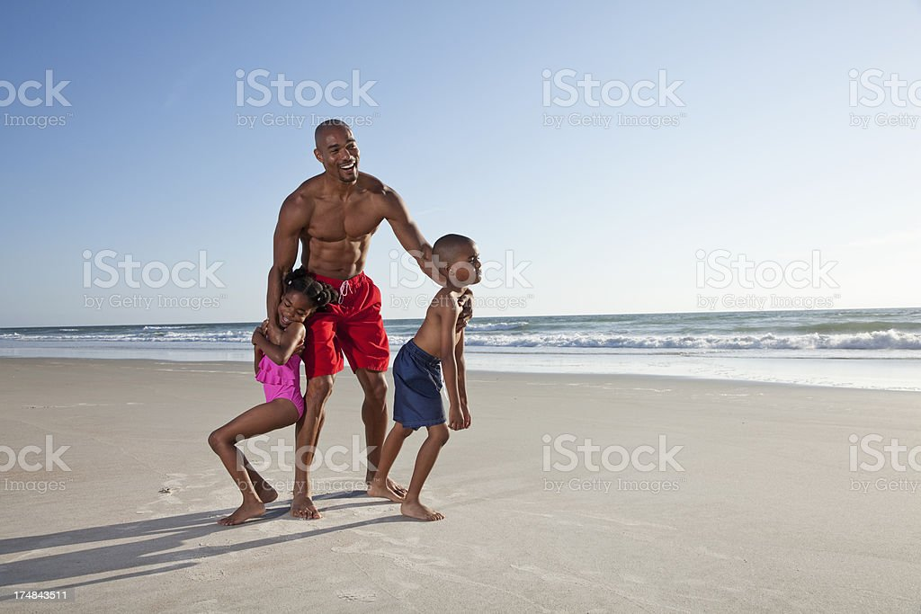 Father and children playing on beach stock photo