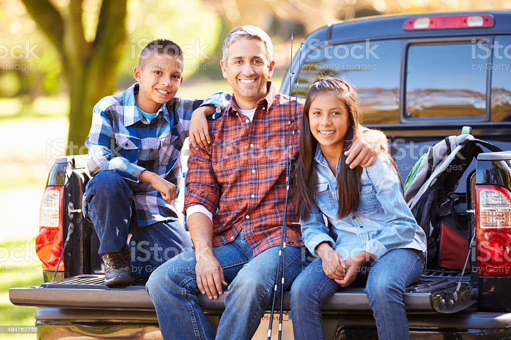 Father And Children Sitting In Truck On Camping Holiday stock photo