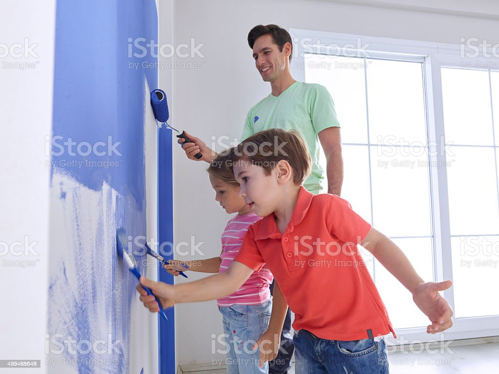 Father and childs painting wall stock photo
