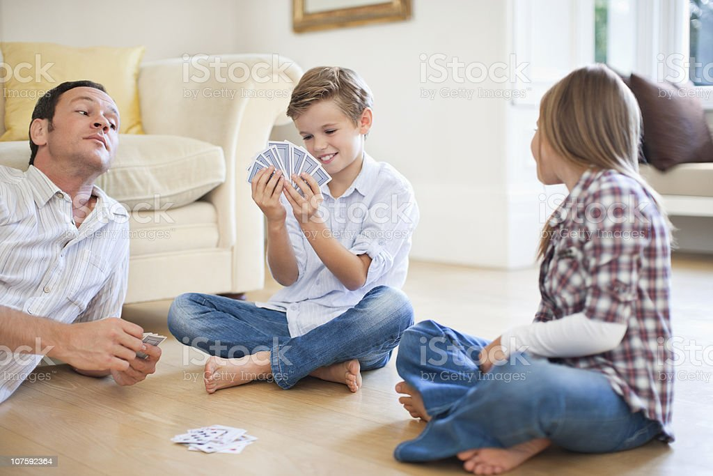 Father and daughter (8-9} peeping into boy's (10-11) cards stock photo