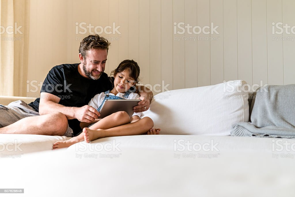 Father and daughter are watching something stock photo