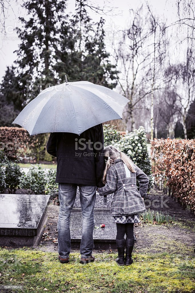 Father and daughter at mummy's gravestone stock photo
