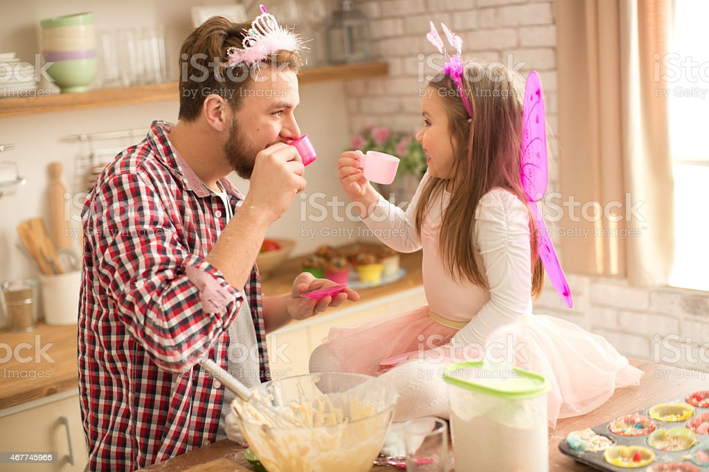 Father and daughter baking and having tea party in kitchen. stock photo