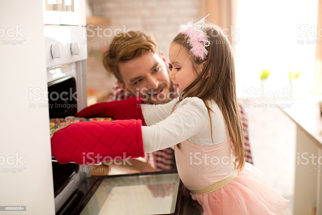 Father and daughter baking in kitchen. stock photo