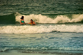 Father and daughter body surfing
