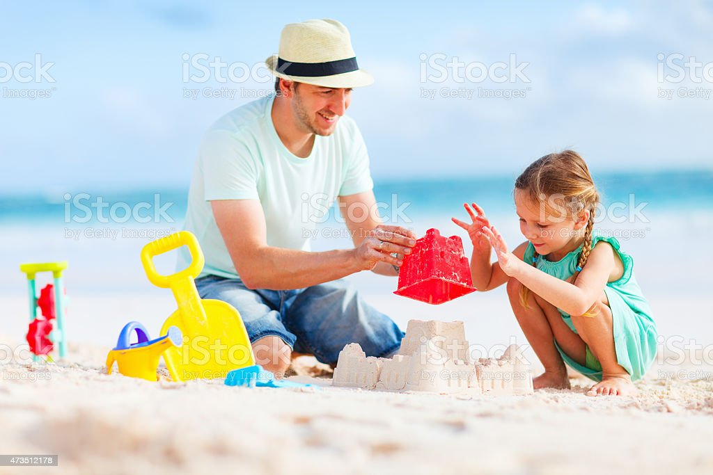 A father and daughter building a sand castle stock photo