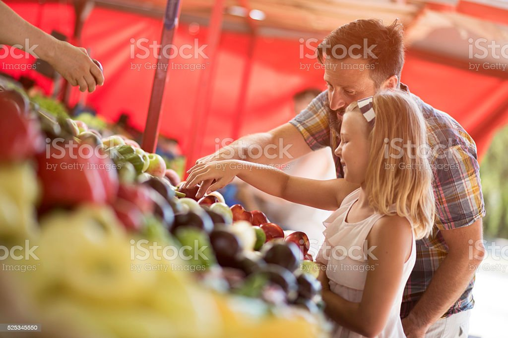 Father and daughter buying on farmers market stock photo