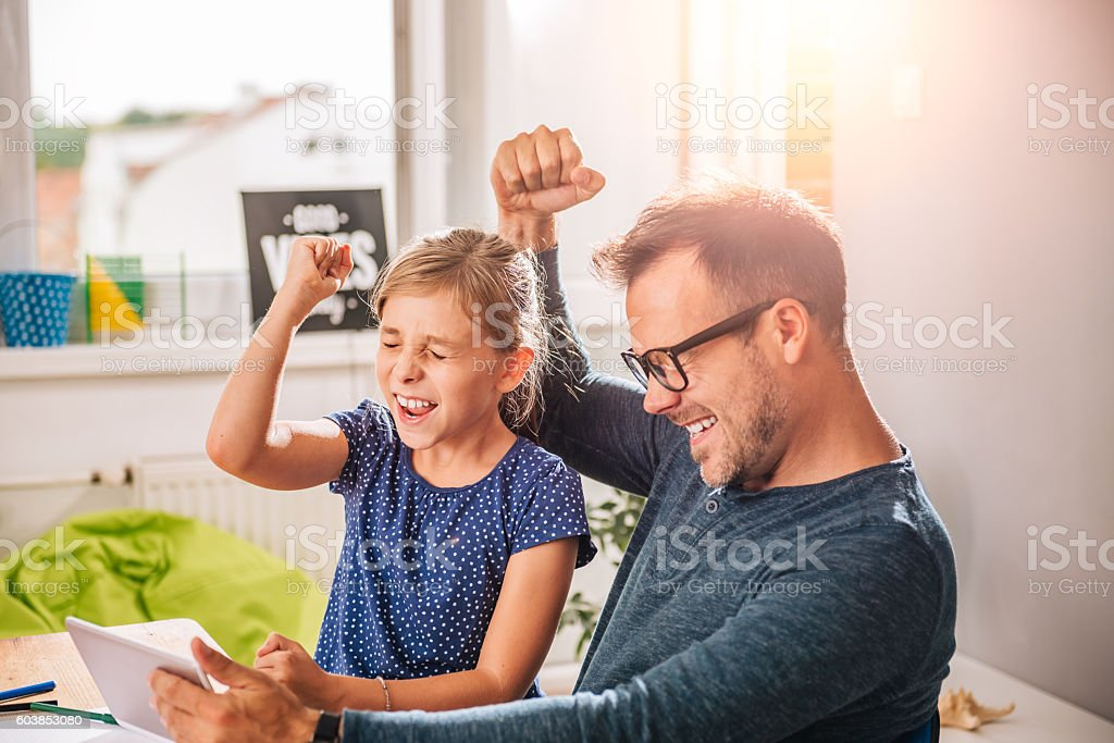 Father And Daughter Cheering during playing game on tablet stock photo