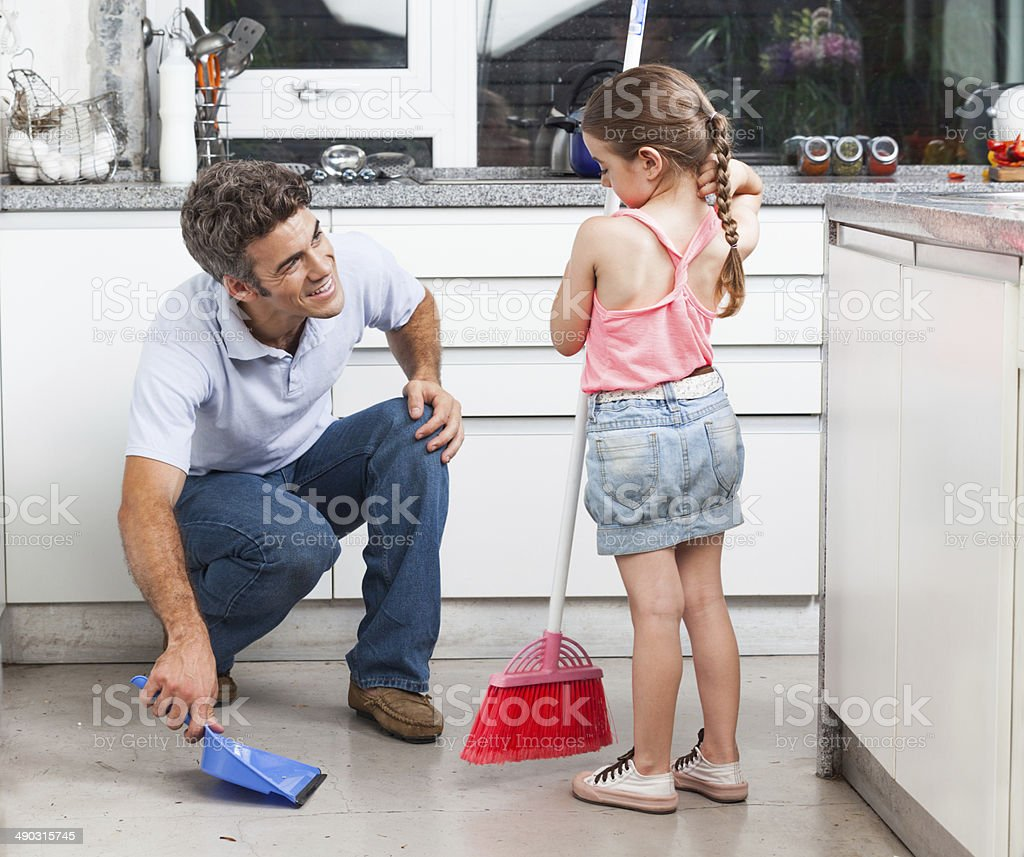 Father and daughter cleaning in the kitchen stock photo