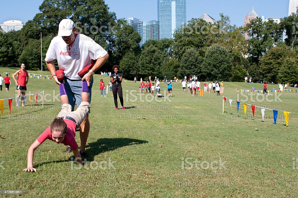 Father And Daughter Compete In Outdoor Wheelbarrow Race stock photo
