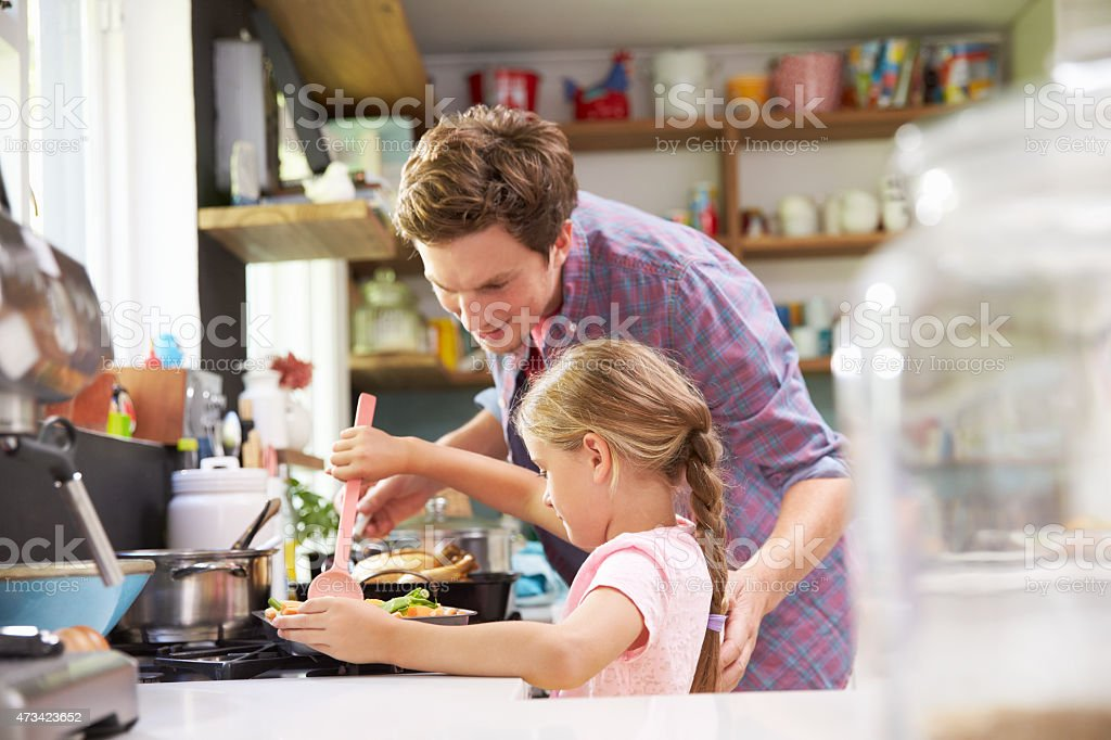 A father and daughter cooking together stock photo