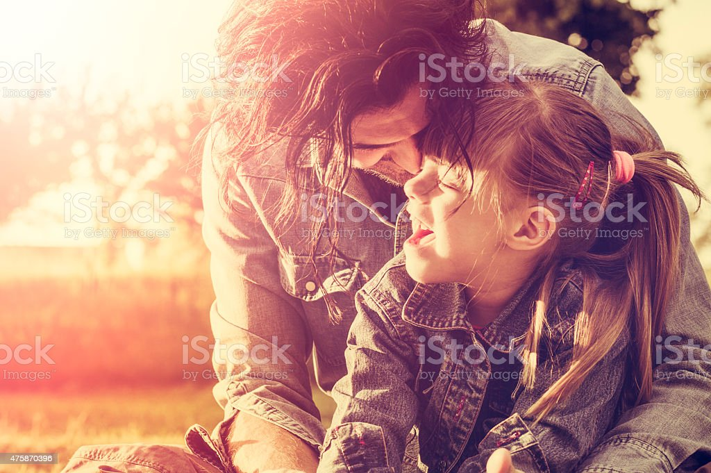 Father and daughter embracing at sunset stock photo