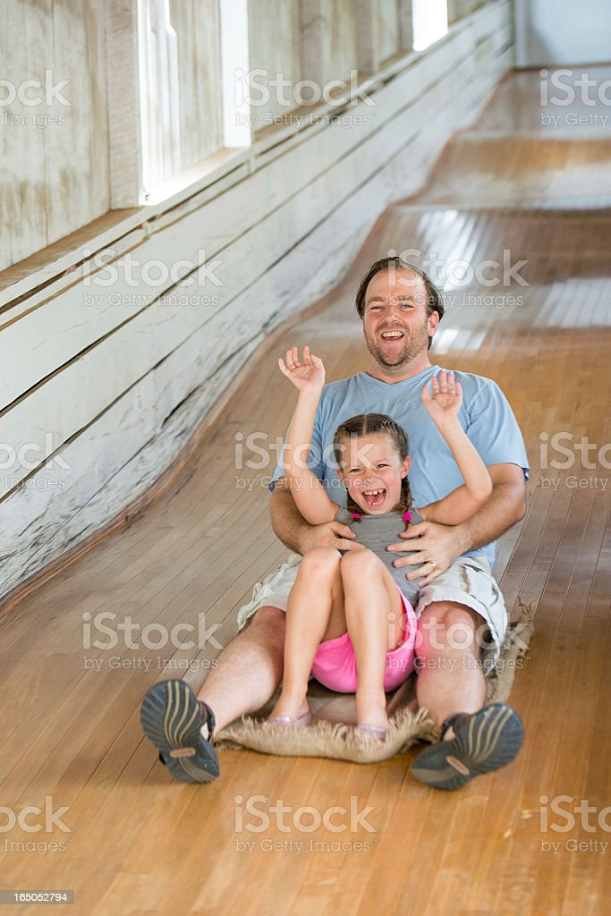 Father and Daughter Enjoy Riding Down a Large Wooden Slide stock photo