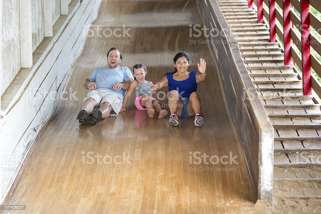 Father and Daughter Enjoy Riding Down a Large Wooden Slide royalty-free stock photo