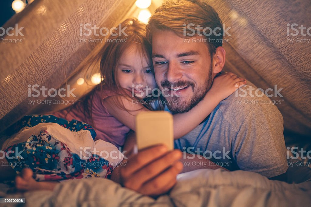 Father and daughter enjoying at home. stock photo