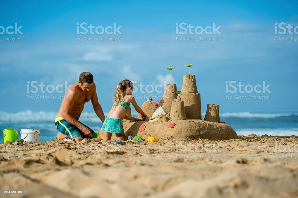 Father and daughter family building sand castle on beach stock photo
