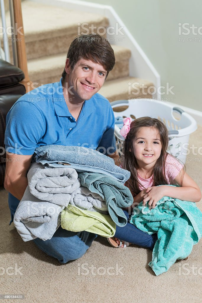 Father and daughter folding laundry stock photo