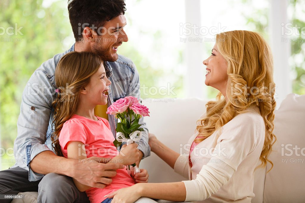 Father and daughter giving flower to mother stock photo
