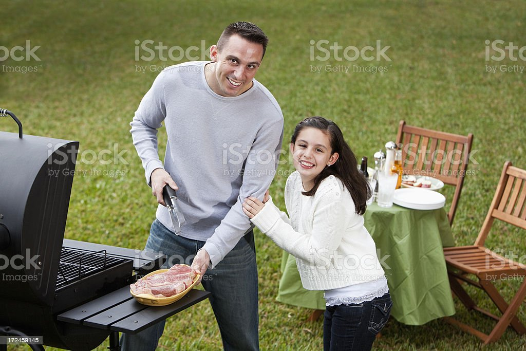 Father and daughter grilling steaks stock photo