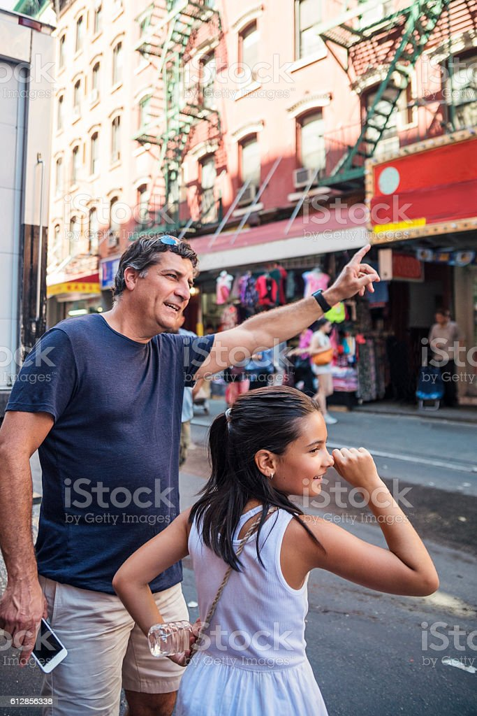 Father and daughter hailing cab in the streets of New-York. stock photo