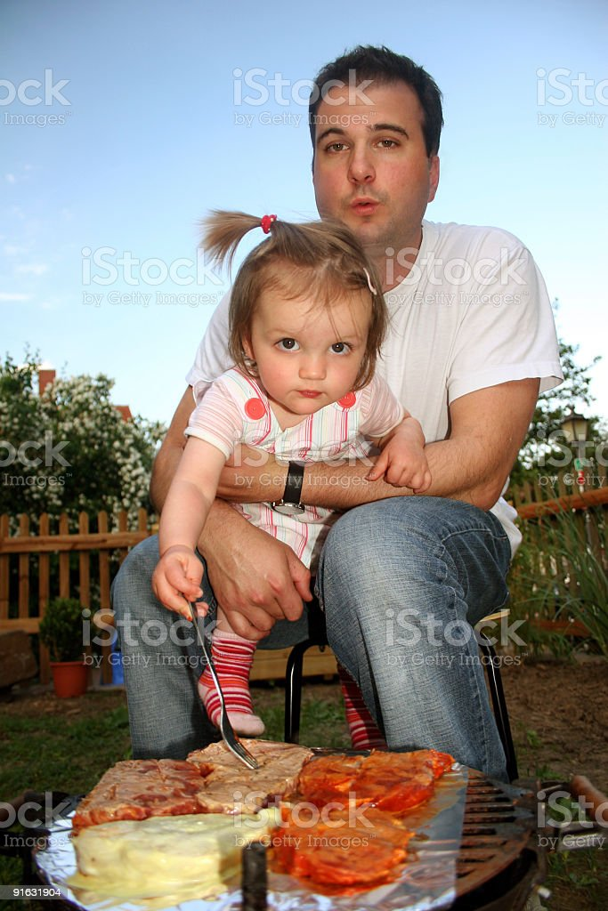 Father and daughter having a barbecue stock photo