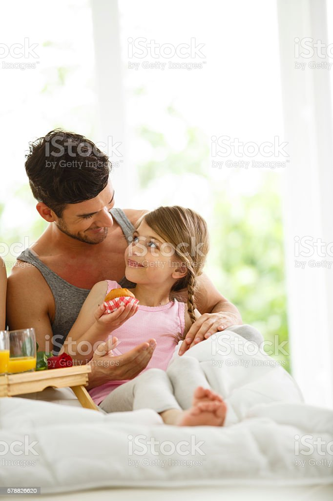 Father and daughter having breakfast in bed stock photo