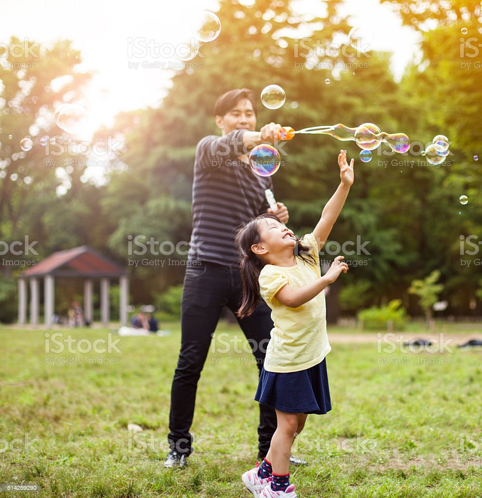 Father and daughter having fun in park with Soap Bubbles stock photo