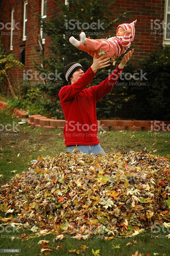 Father and Daughter having Fun in the Leaves during Autumn royalty-free stock photo
