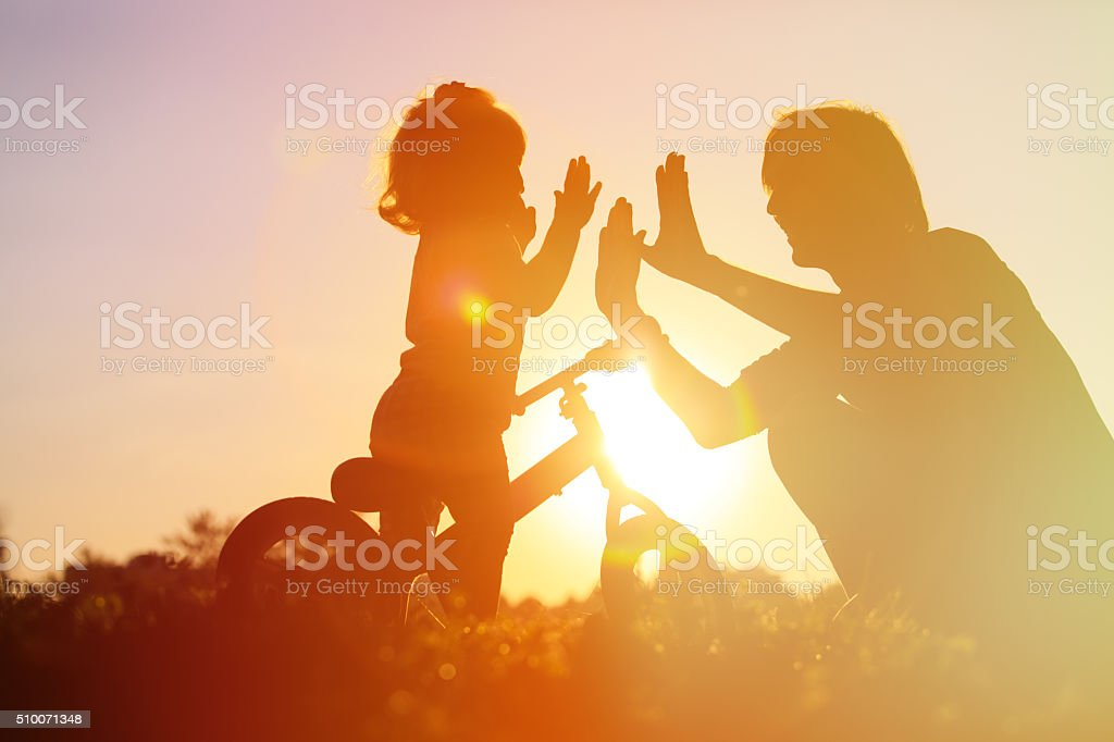 father and daughter having fun riding bike at sunset stock photo