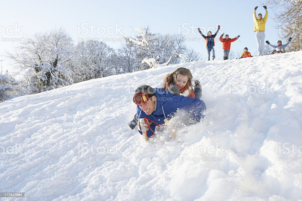 Father And Daughter Having Fun Sledging Down Hill royalty-free stock photo