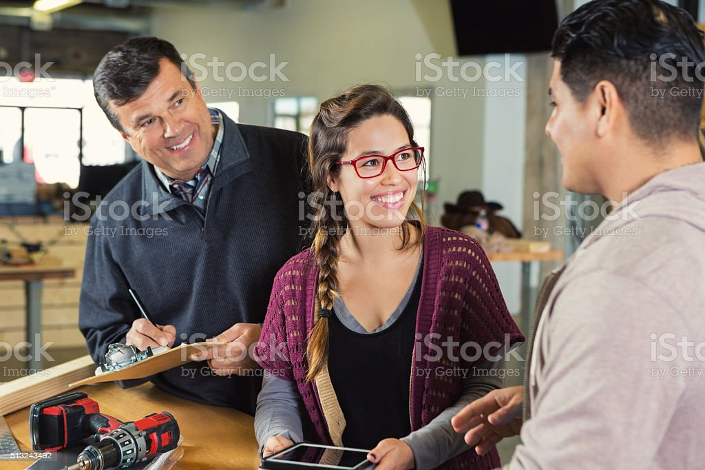 Father and daughter helping customer in small carpentry business stock photo