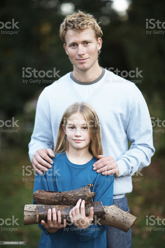 Father and daughter (7-9) holding firewood, portrait royalty-free stock photo