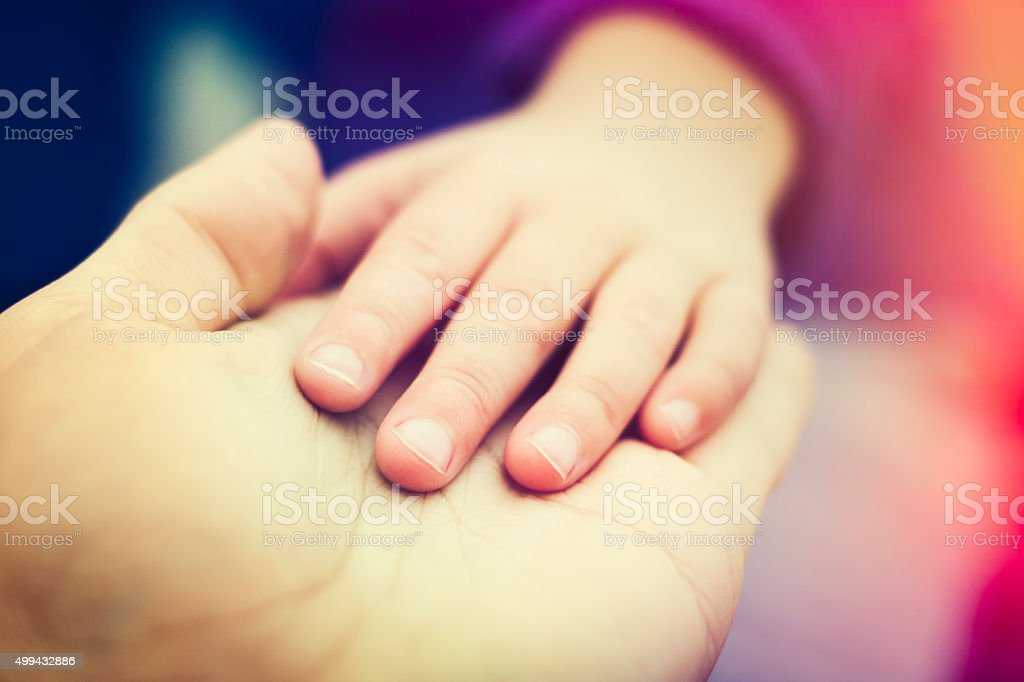Father and daughter holding hands closeup stock photo