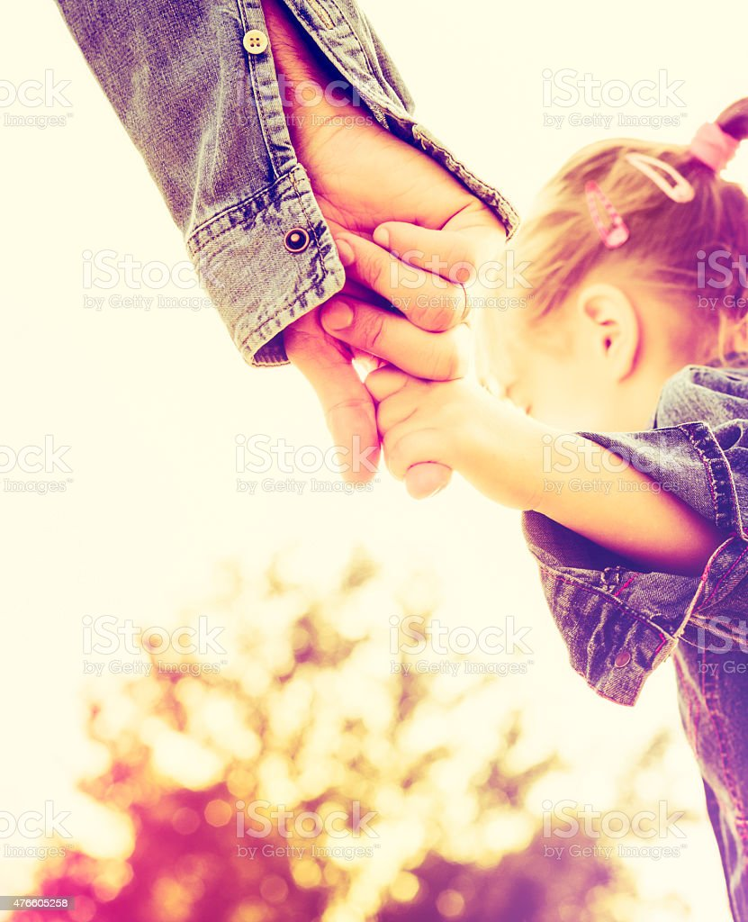 Father and daughter holding hands together stock photo