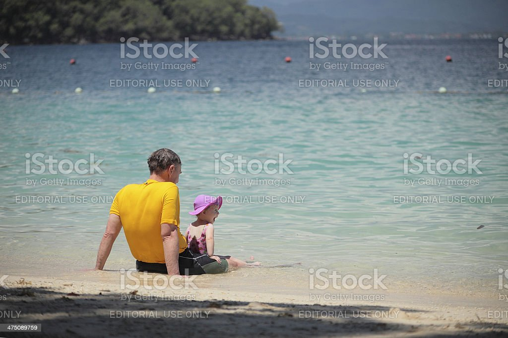 father and daughter in a beach stock photo