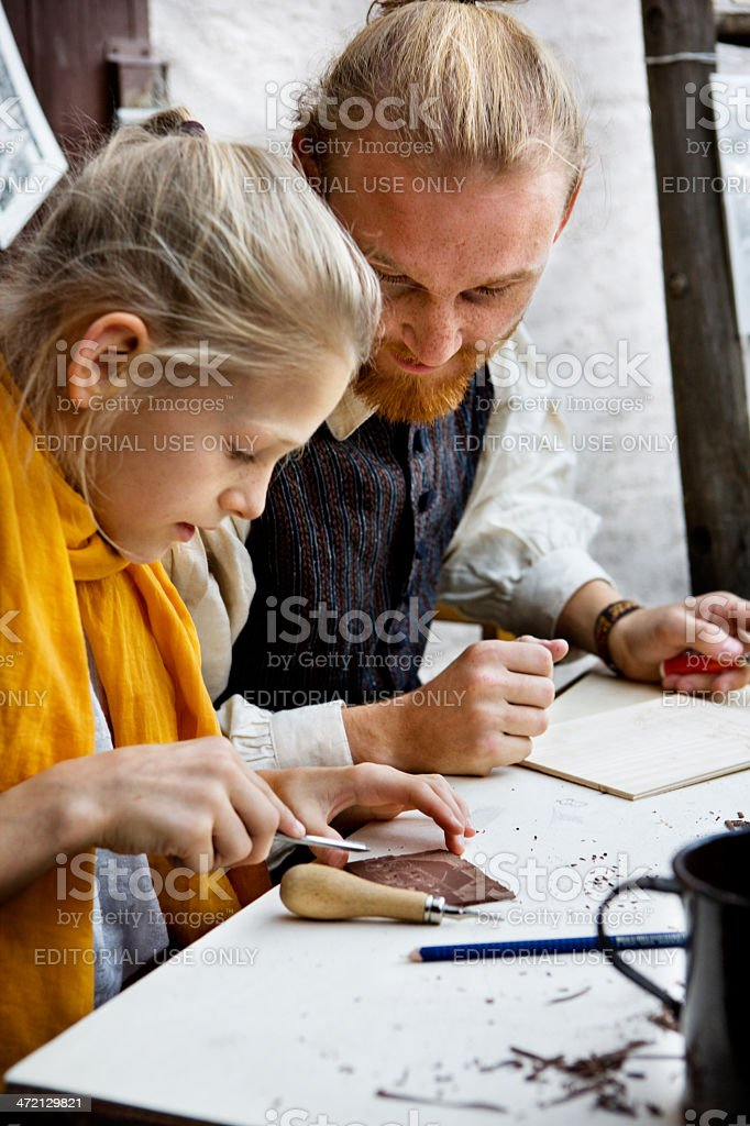 father and daughter in historic clothing showing traditional handcraft stock photo