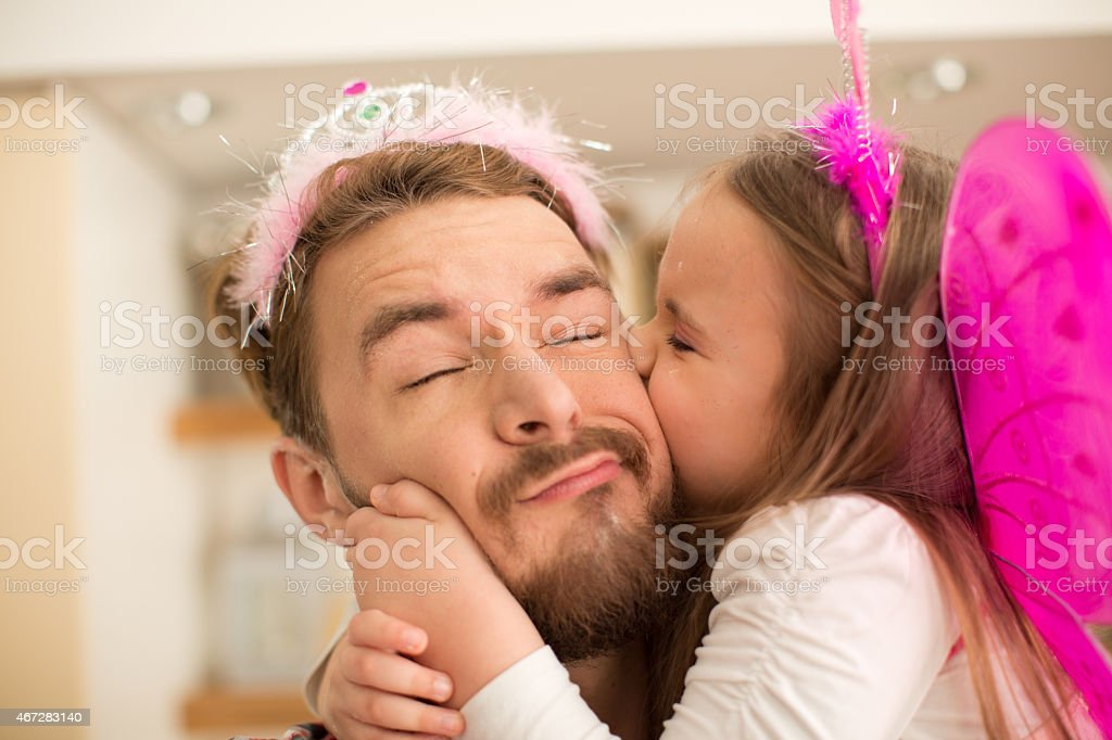 Father and daughter in kitchen taking selfies. stock photo