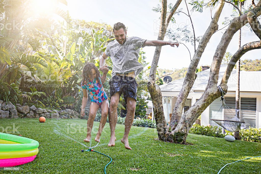 Father and daughter jumping in sprinkler at backyard garden stock photo