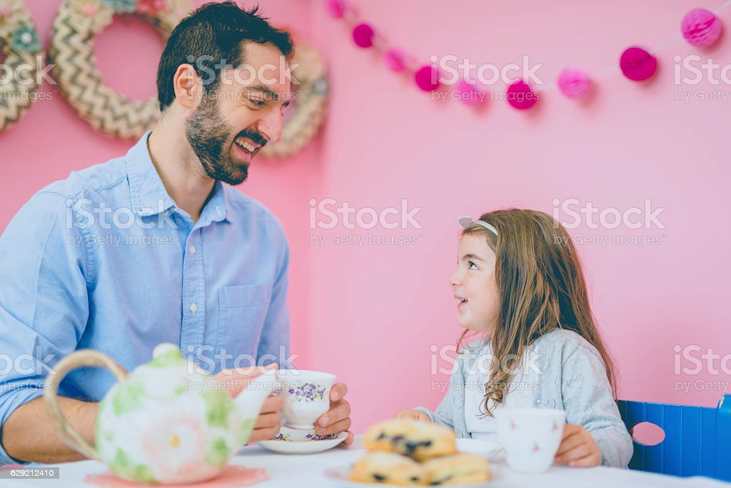 Father and daughter laughing during their adorable tea party together stock photo